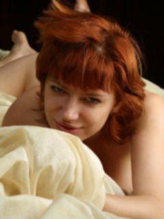 Обнаженная рыжая женщина в постели